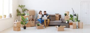 happy couple in their new apartment flanked by boxes of their belongings