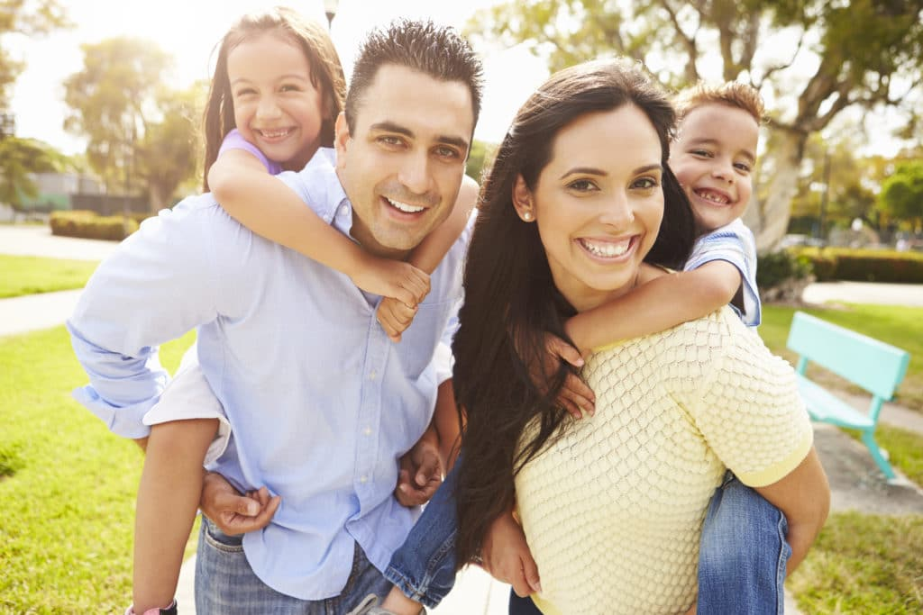 a happy hispanic family smiling outside of their apartments for rent