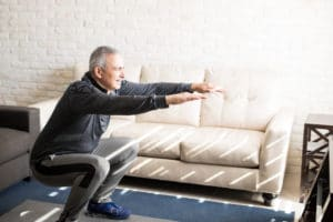 Senior gentleman does squats and bodyweight exercises in his apartment to lose weight