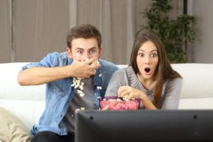 young couple watching television and eating popcorn