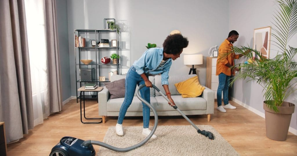 young nice happy married couple cleaning living room in apartment, wife vacuuming carpet floor while husband wiping dust on furniture behind, family concept, routine life